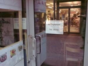 """Schild an der Tür eines Geschäfts: """"Mittagspause bis 18 Uhr"""""""